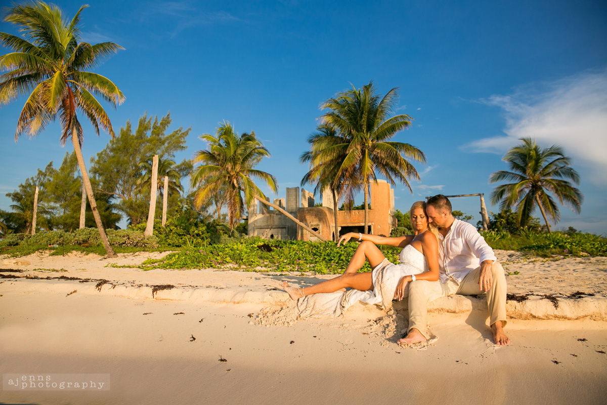 The couple sitting on the shore with Mexican ruins in the background