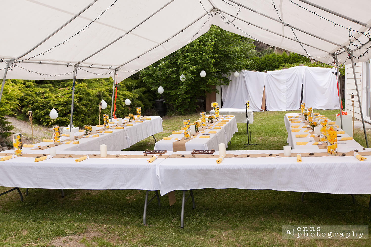 The reception tent all setup with yellow trim and floating candles