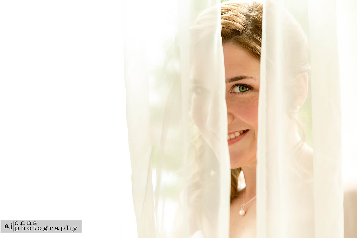 The bride peering through the sheer curtains