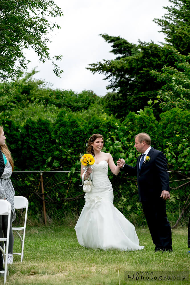 Father of the bride holding the brides hand while he walks her down the isle