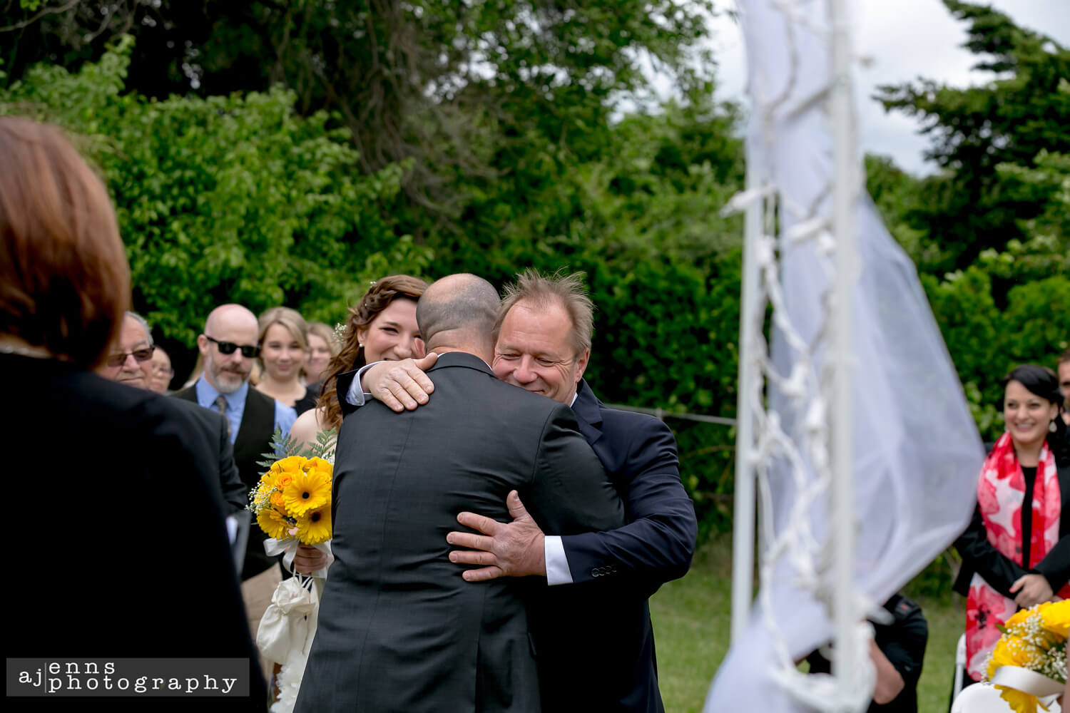 Father of the bride hugging the groom as he gives away his daughter