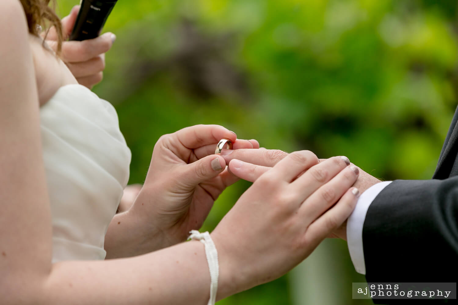 The bride putting on the grooms ring with her reflection in his ring
