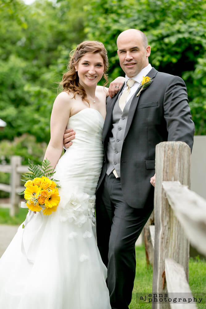 The newly weds leaning against a wooden fence