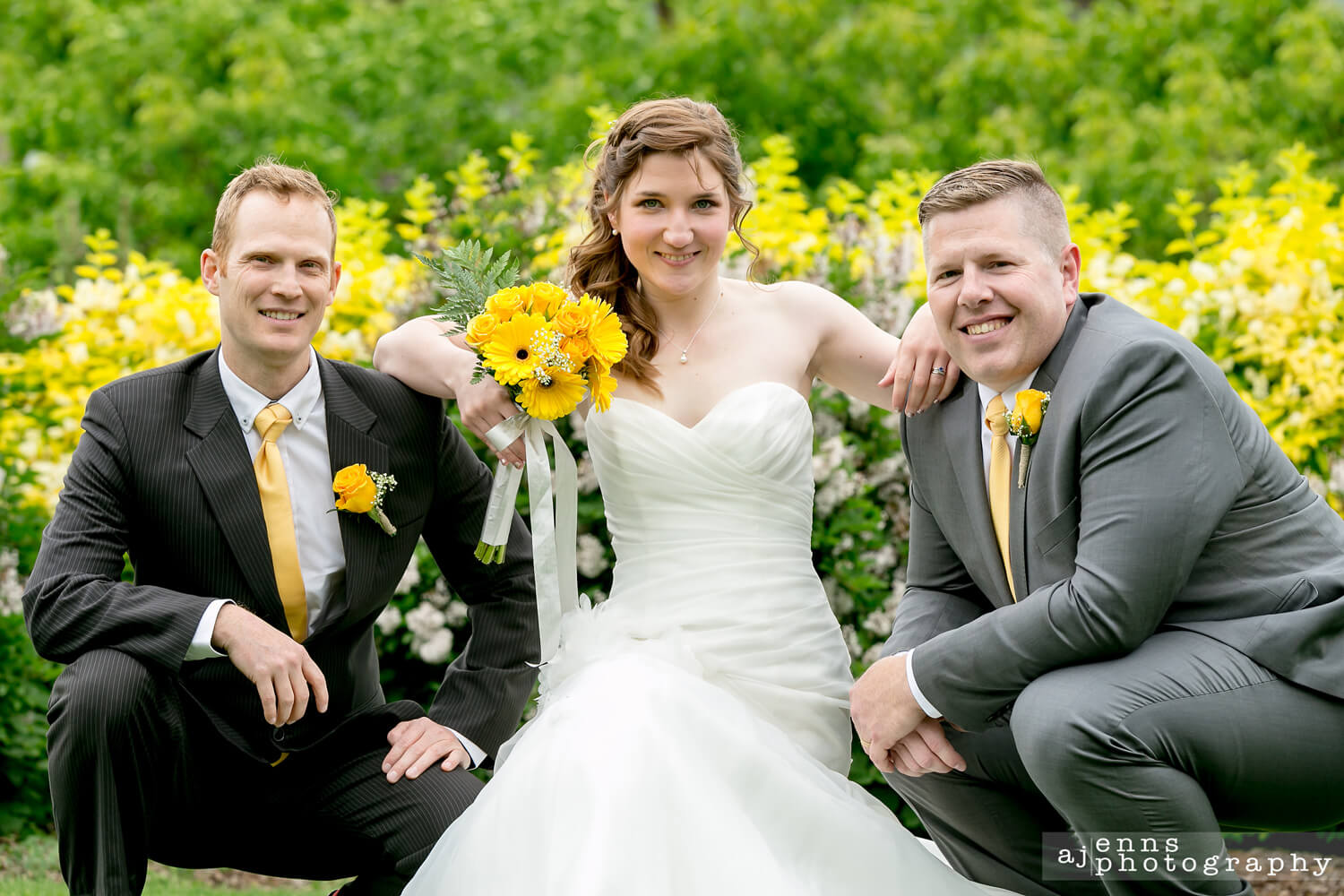 The bride crouching in the grass leaning on the groomsmen