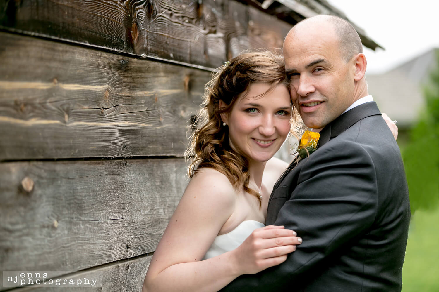 The beautiful bride and groom leaning against a wooden wall