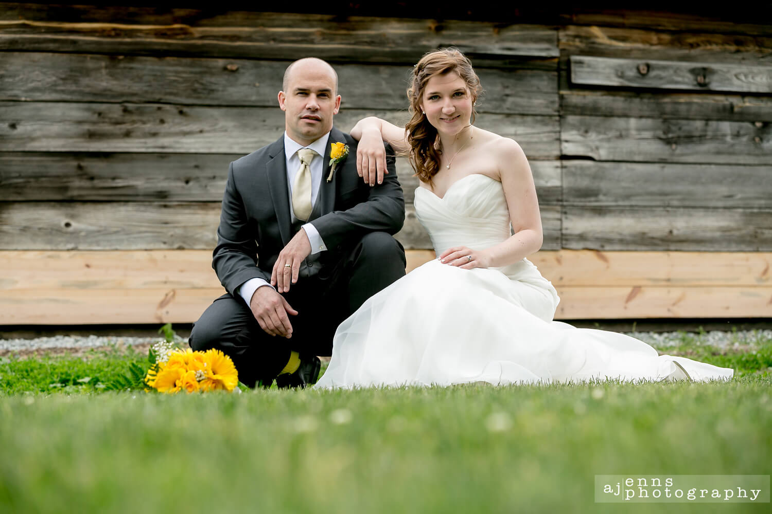 The bride and groom crouching in the short grass