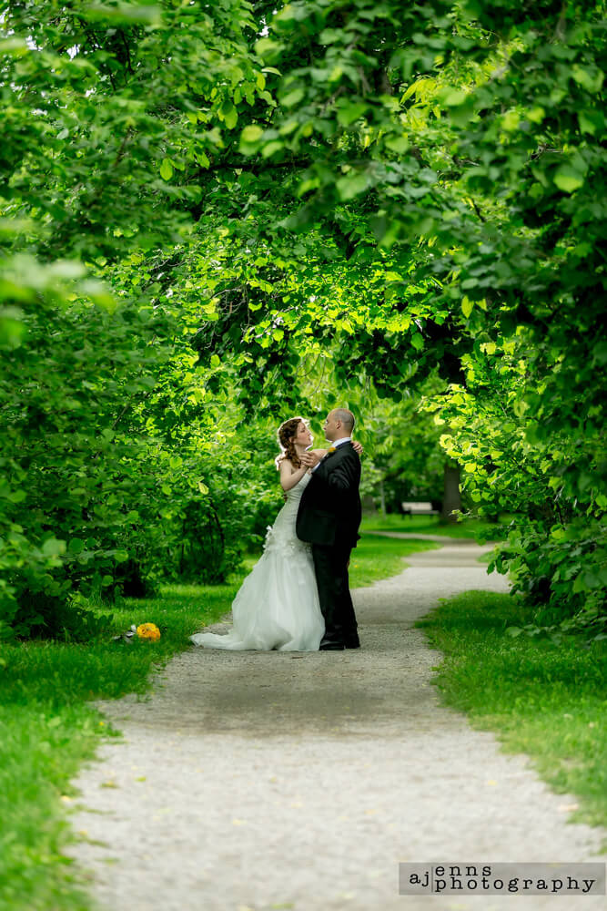 The newlyweds dancing under a tree canopy over a path