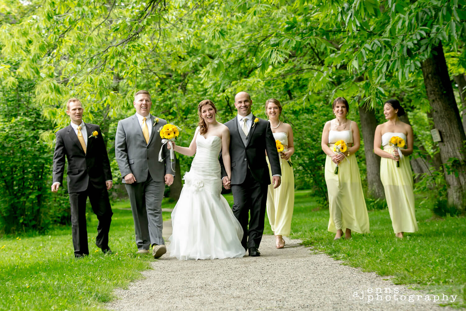 The entire wedding party walking down a path having a party