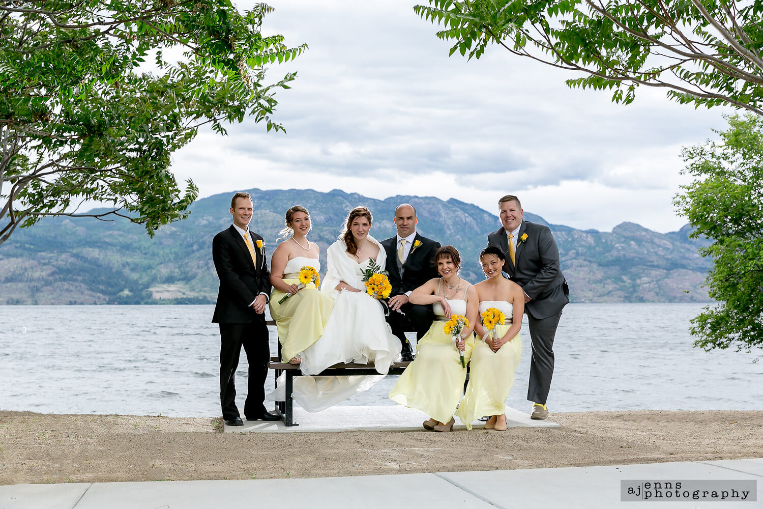 The couple sitting on a picnic table over looking Kelownas lake with the mountains in the background.