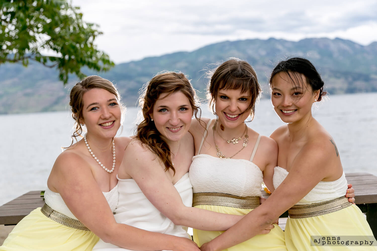 The bride and her ladies in front of a lake with the wind blowing