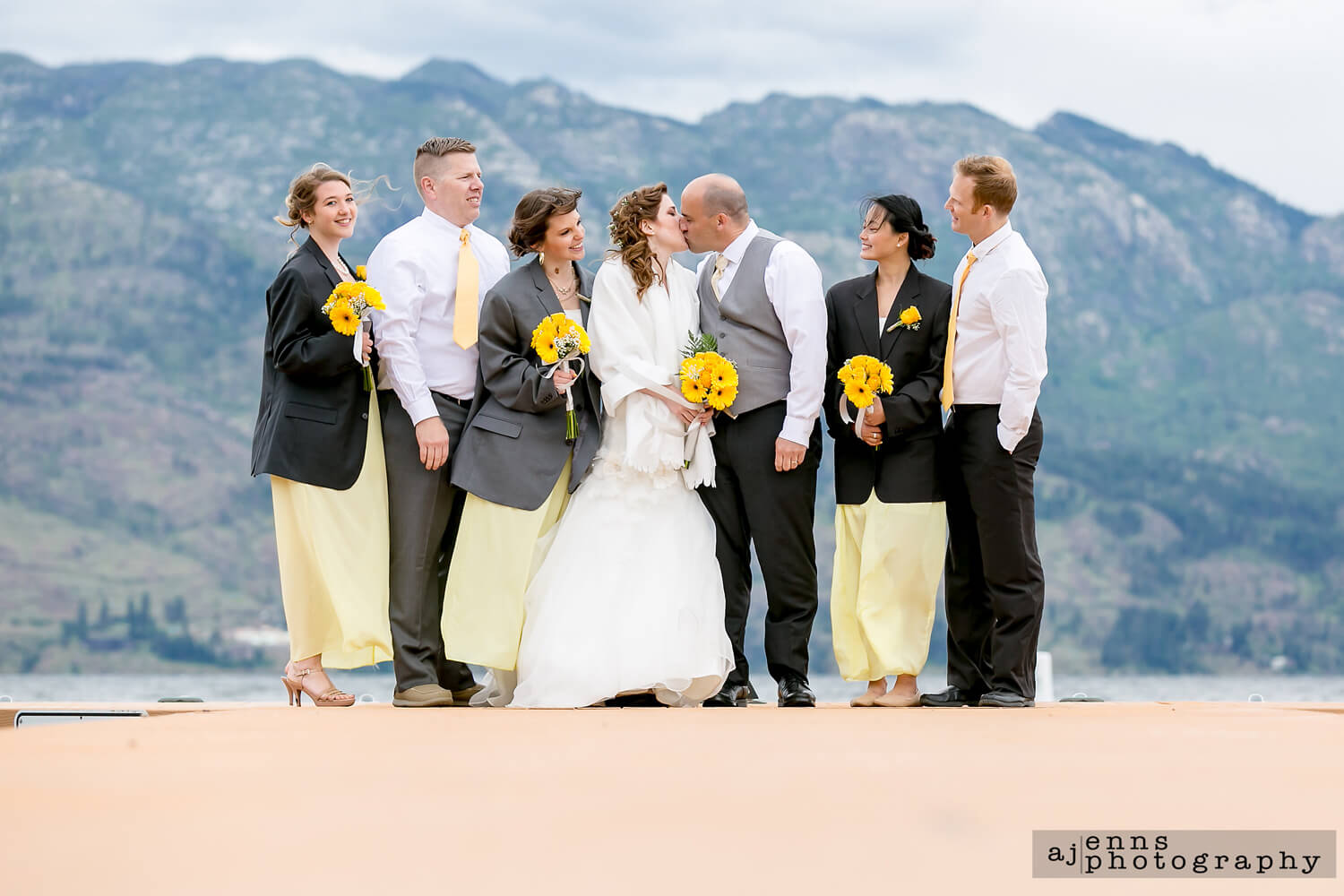 The wedding party standing at the end of a peer in Kelowna