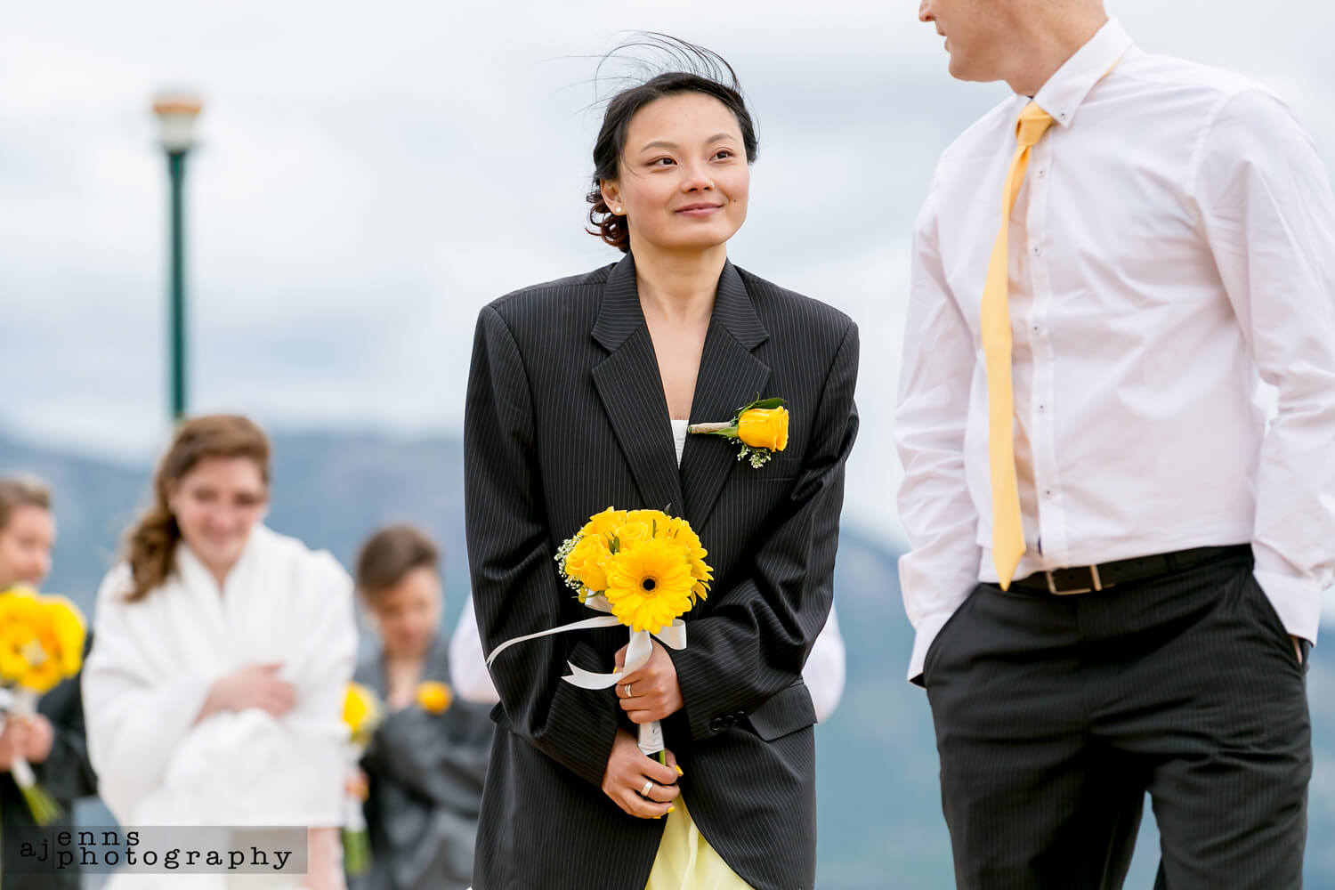 One of the bridesmaids wearing a groomsmen' jacket