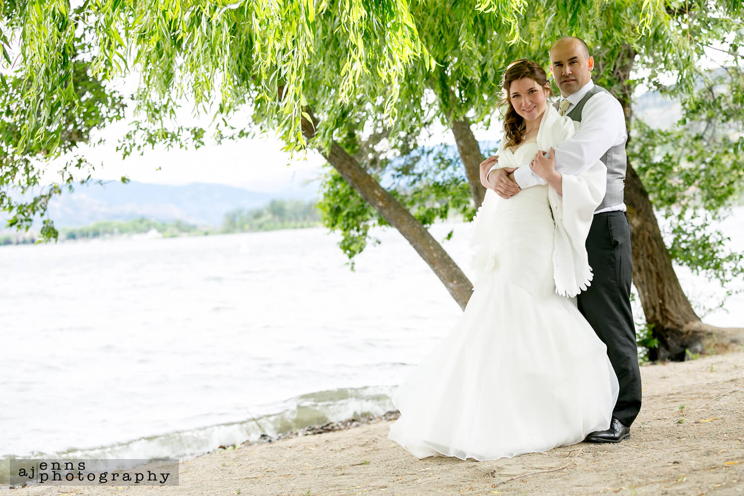The couple standing under a massive willow tree on the waters edge