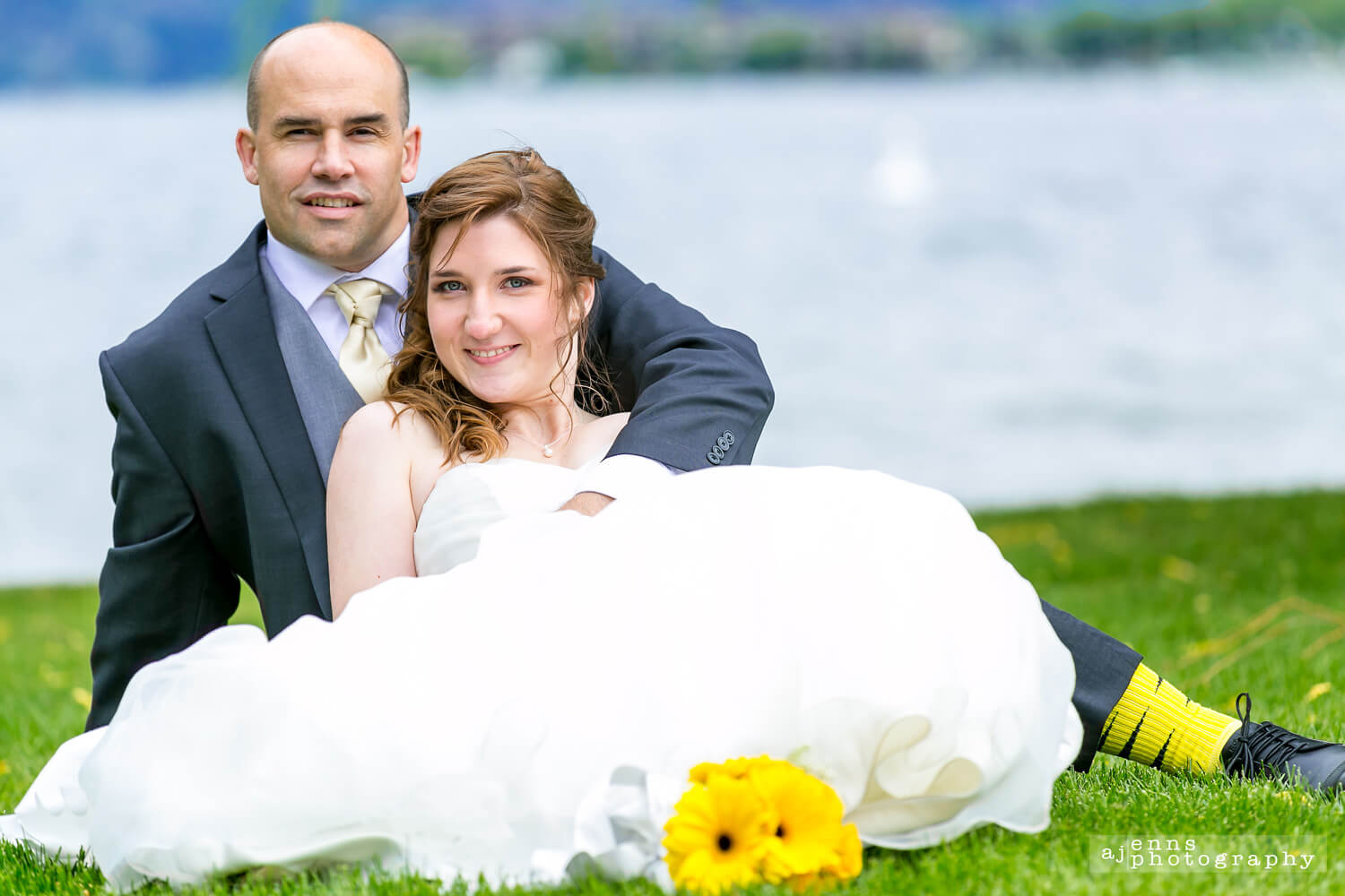 Bianca and Scott sitting in the grass by the lake