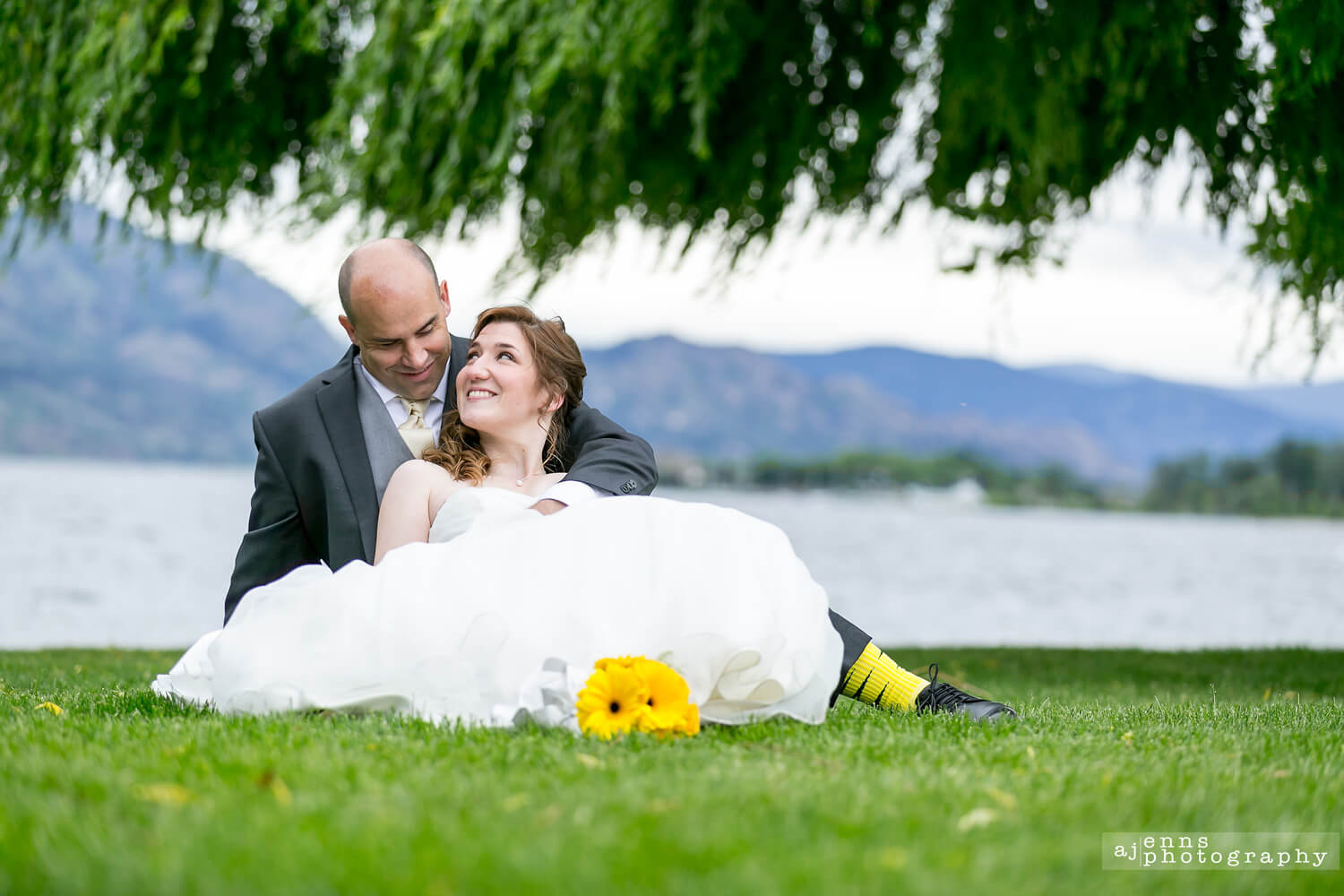 The bride and groom sitting in the grass by the lake in Kelowna B.C.
