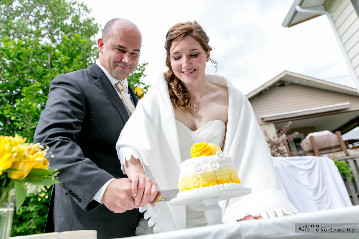 Bride and groom cutting the yellow wedding cake