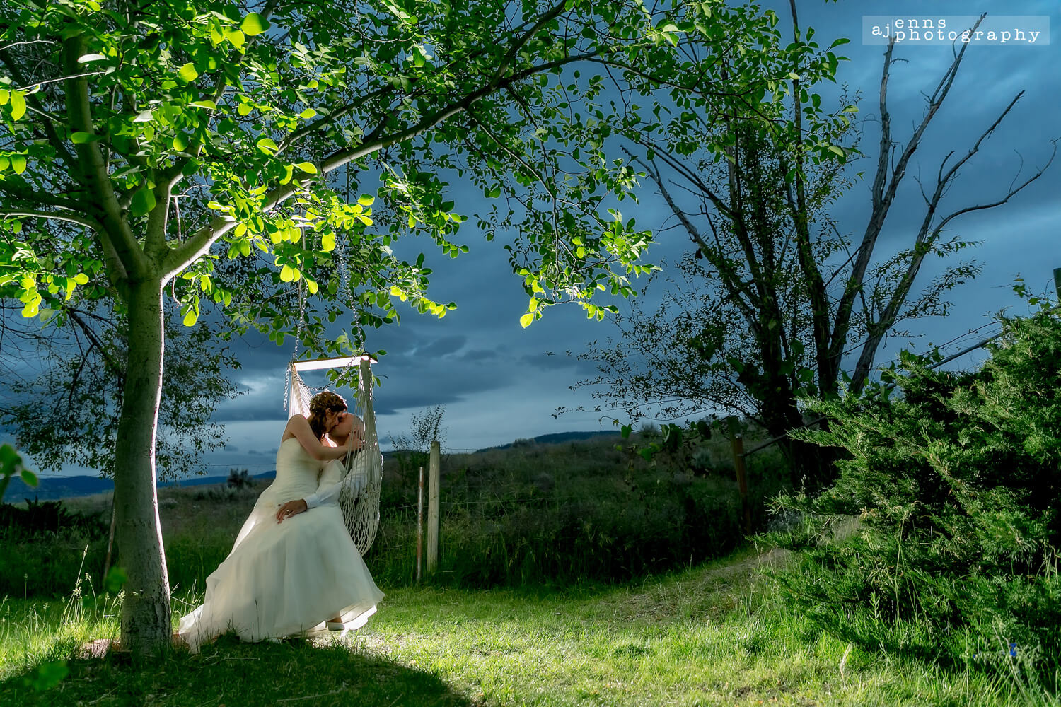 The bride sitting on the groom in a hanging hammock chair at dusk