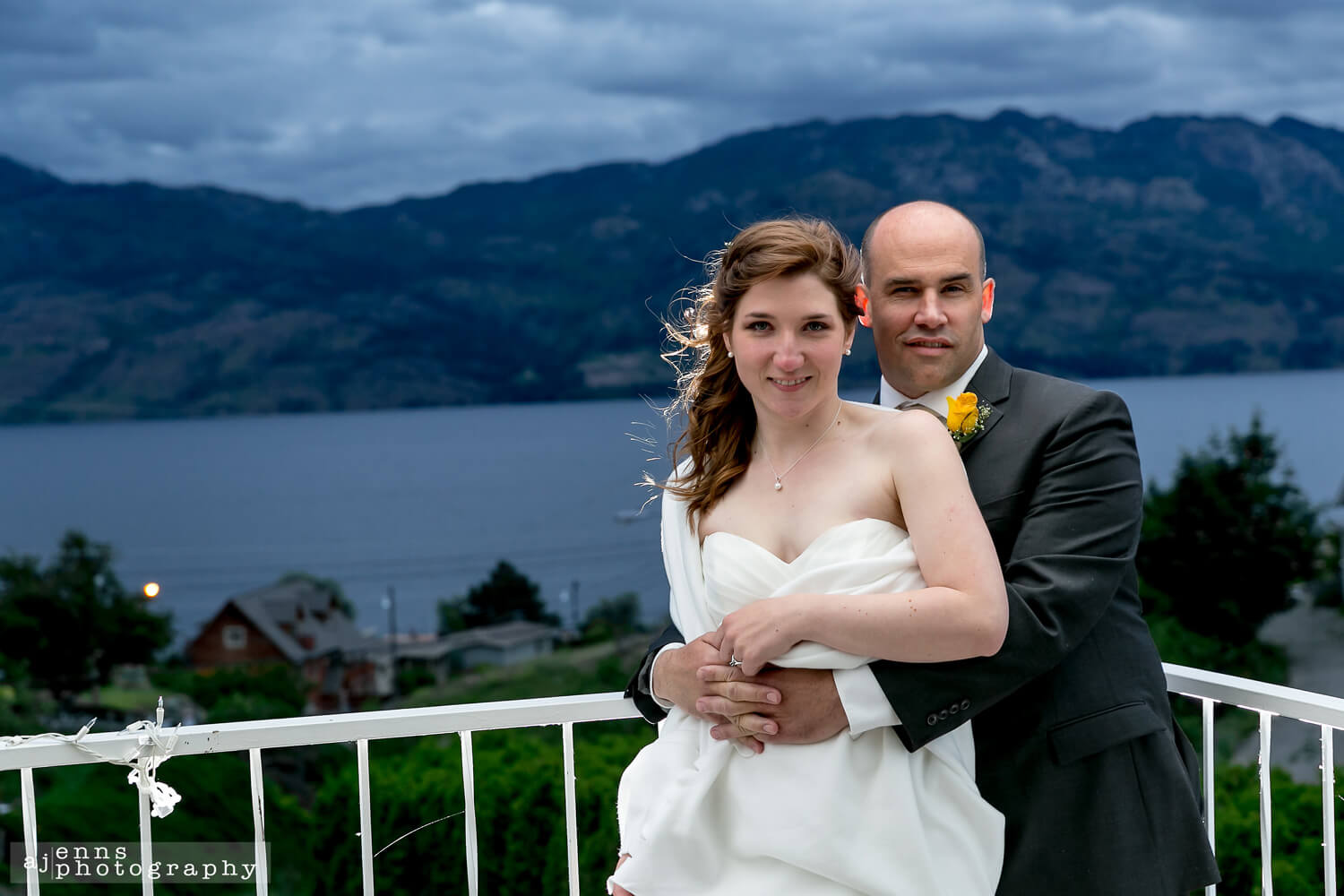 the bride and groom being back lit on the deck over looking the lake