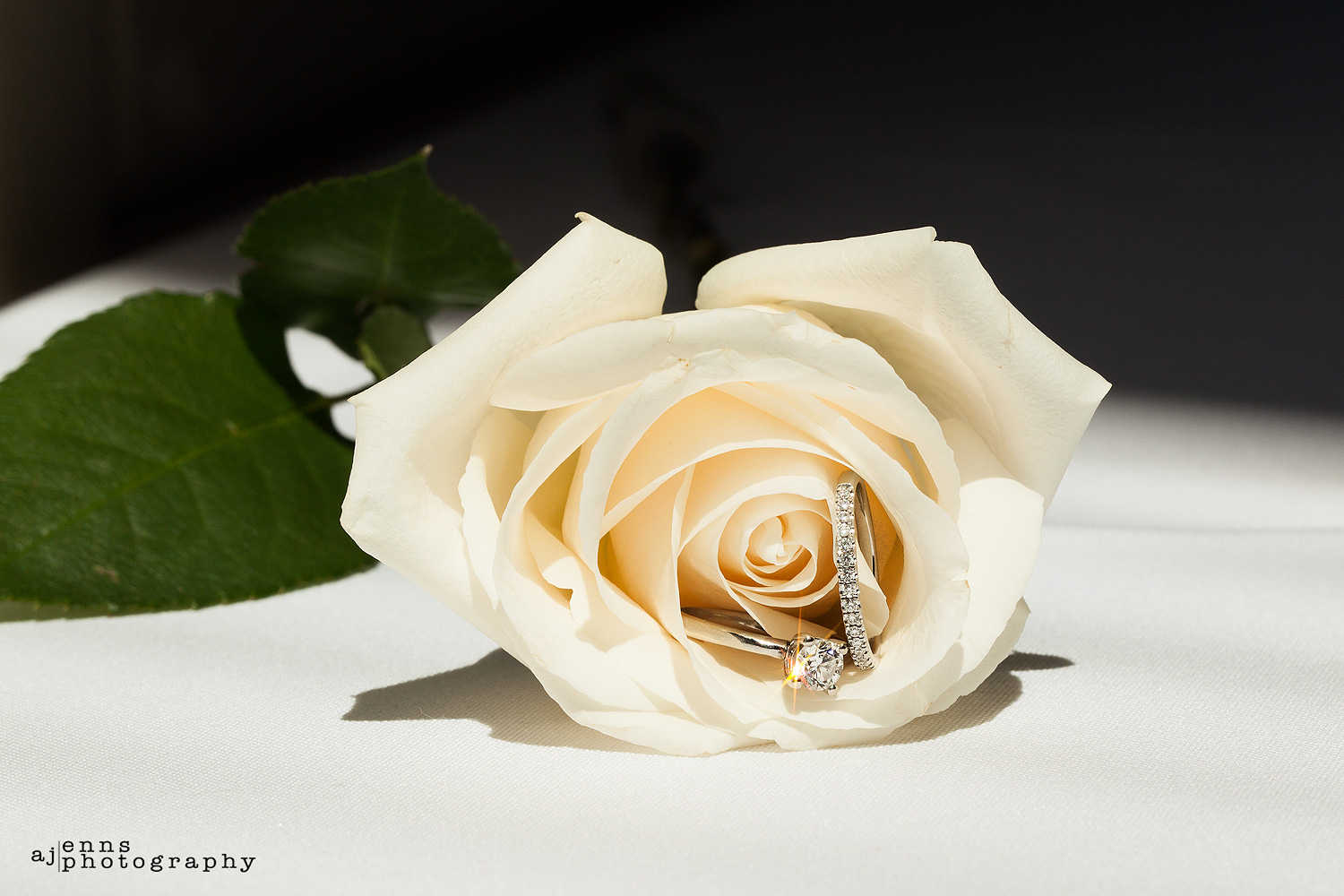 the rings nestled in a white rose for the grooms mother who passed away