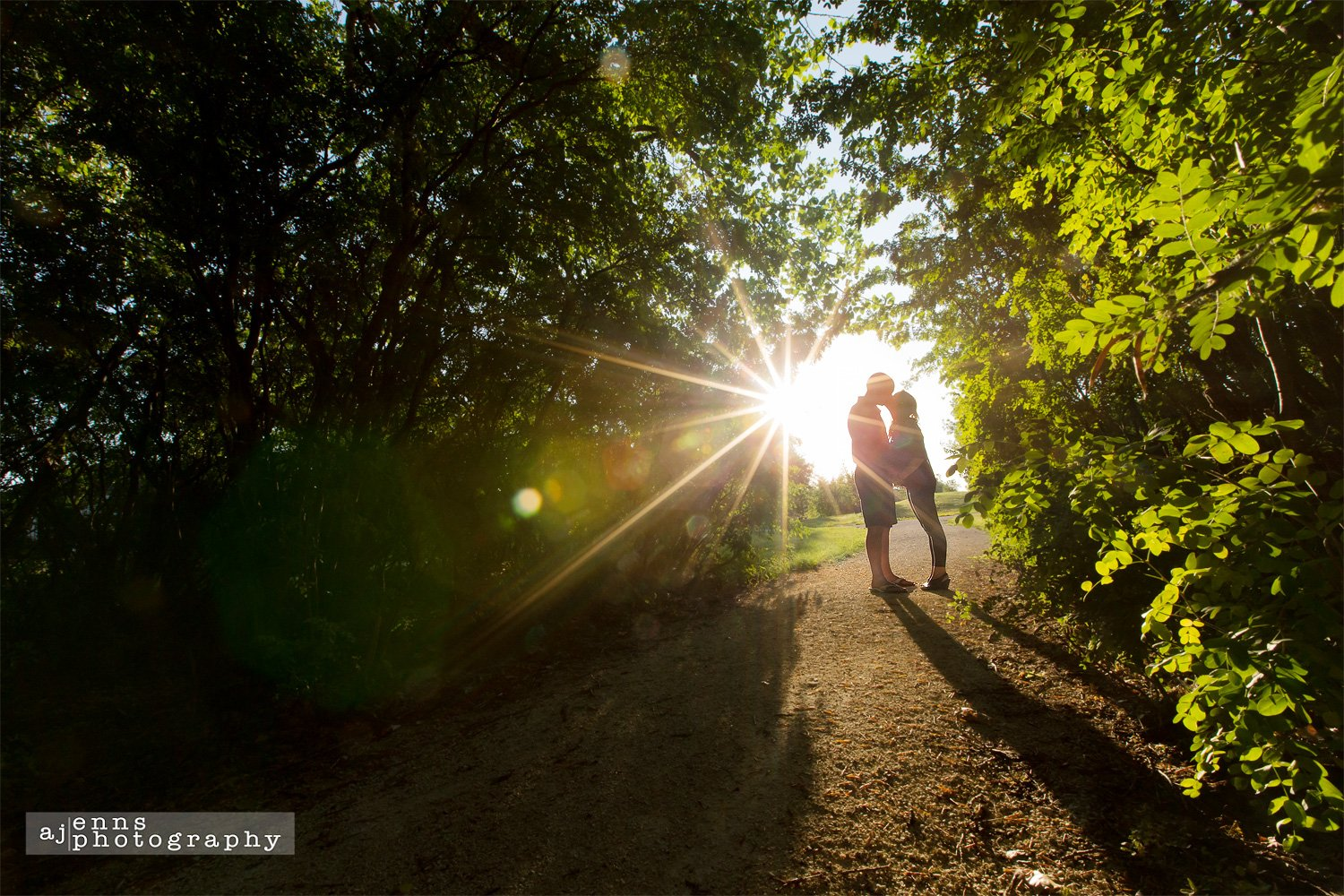 A special kiss during sunset under a canopy of trees
