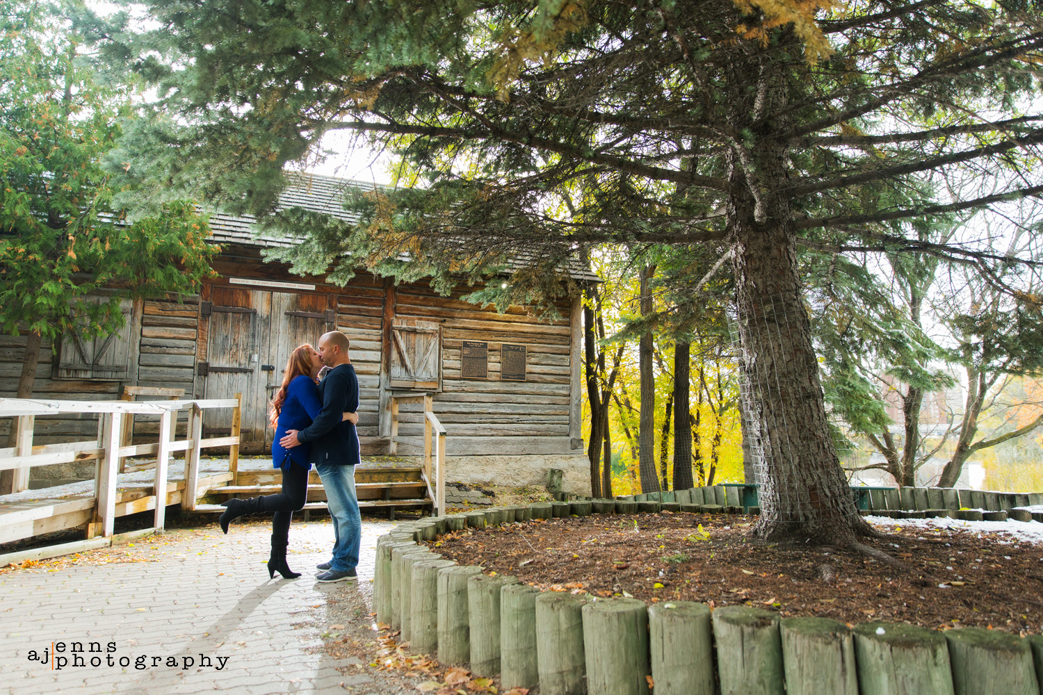 The couple kissing under spruce tree in front of Grant's old mill