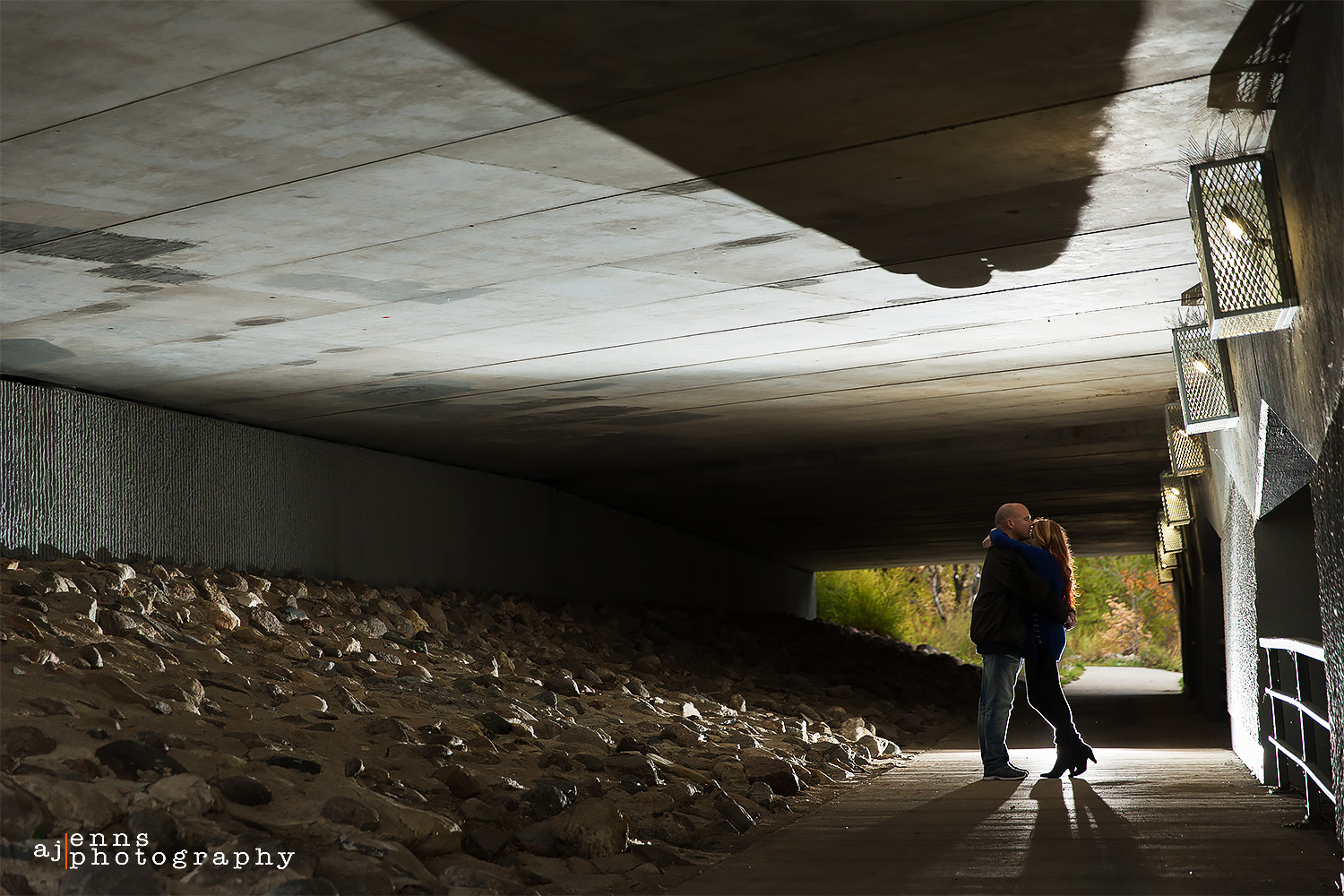 The couple embracing while being back lit under a portage avenue bridge