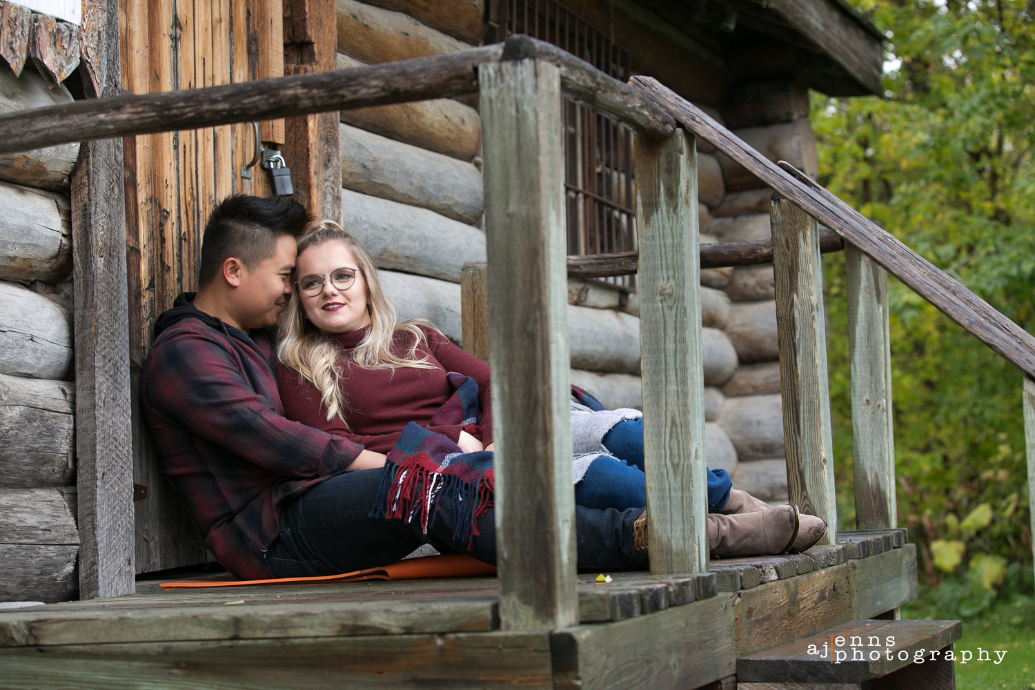 Engagement photos sitting against a log cabin on the steps
