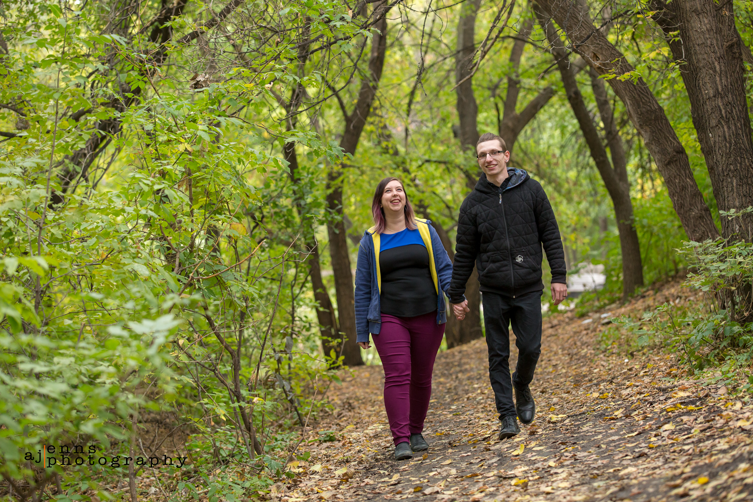The couple walks holding hands down a leaf filled path