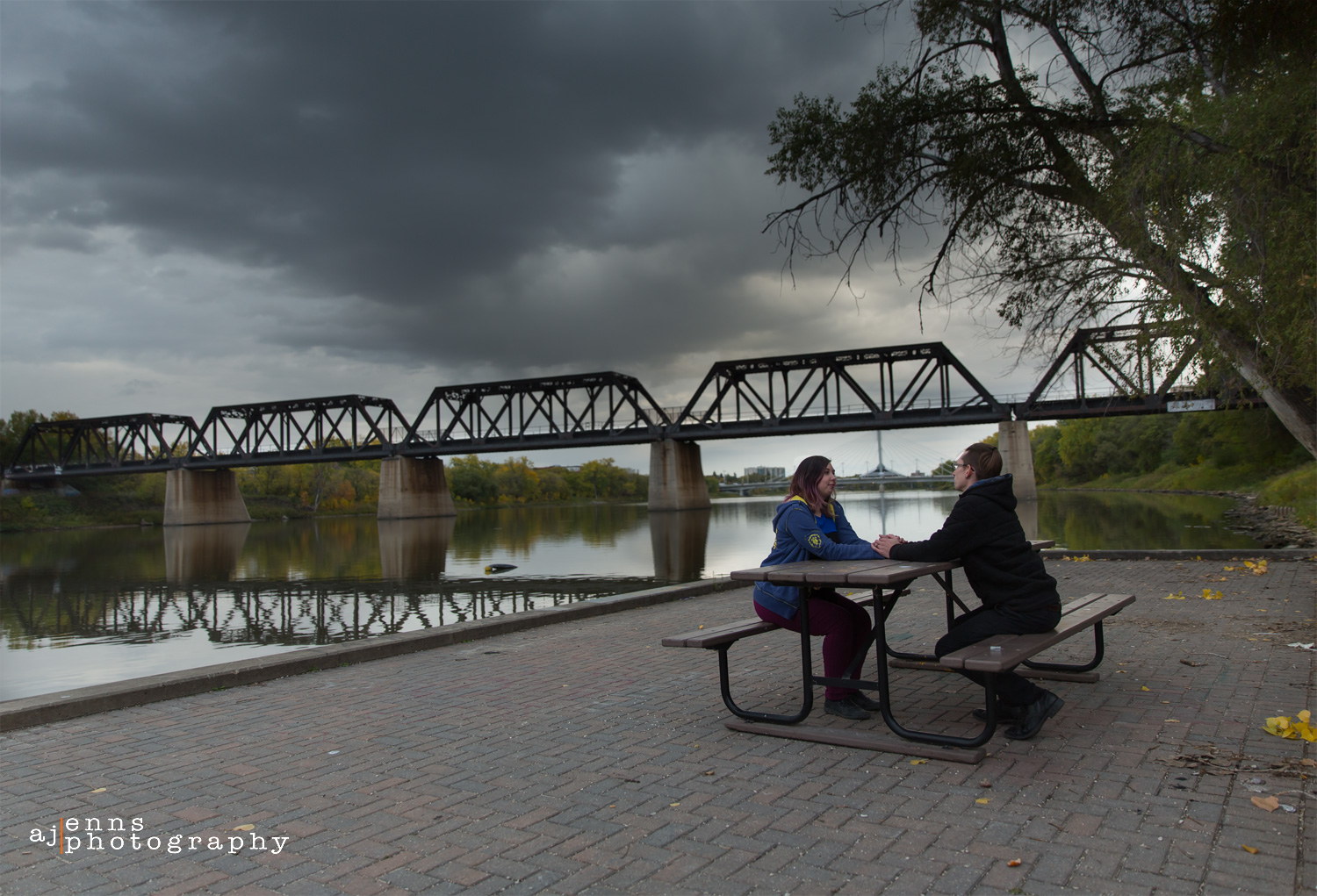 Sitting on a picnic table under some stormy clouds with a train bridge in the background